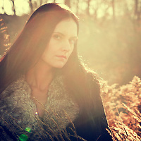 atmospheric photo of beautiful young caucasian woman in retro fashion style on the meadow with warm light
