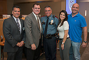 Houston ISD superintendent Dr. Terry Grier and Officer Gilbert Garcia pose for a photograph with Garcia's family after he was recognized during a Central Office staff meeting, April 8, 2014.
