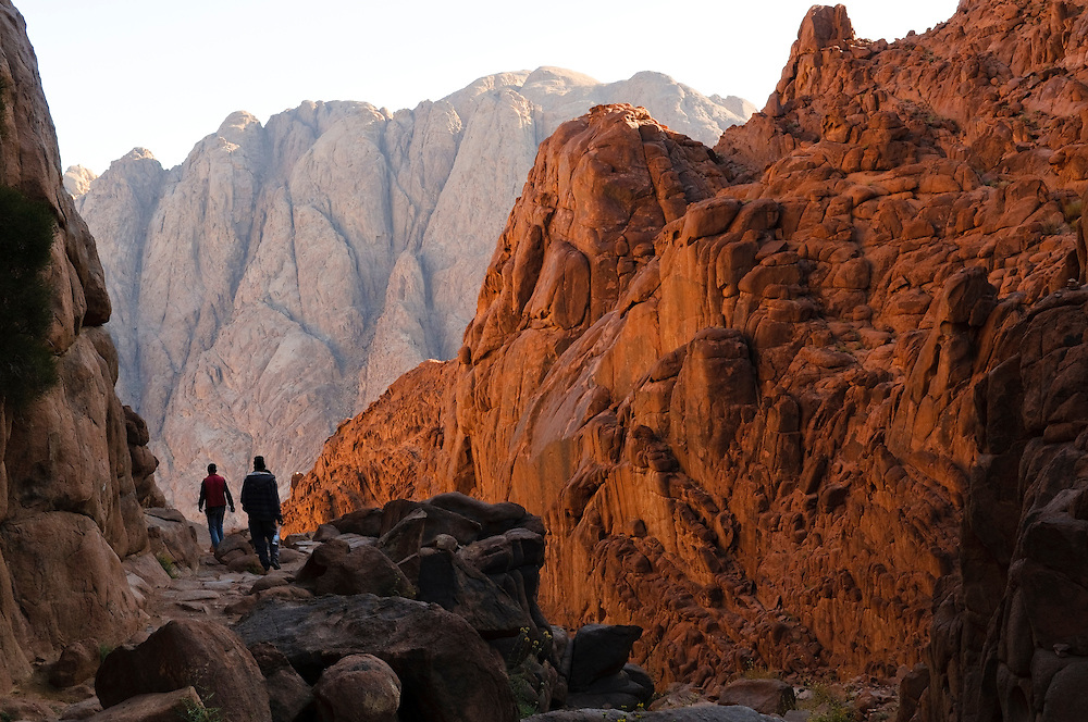 Three hikers descending Mount Sinai in early morning. There are two primary routes up and down the mountain. These hikers are descending via the Steps of Penitence route. The mountain, associated with Moses and the Ten Commandments, is a popular travel destination for religious and secular visitors alike.<br />