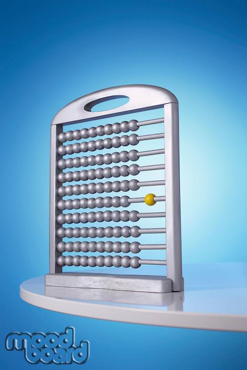 Single yellow bead on silver abacus in studio