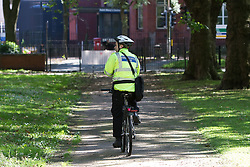 © Licensed to London News Pictures. 23/07/2012. Manchester , UK . A PCSO on a bicycle searches grassy areas around Whitworth Park . Police report that two sisters have gone missing from their home . Liana Boyd , 11 and Teigan Boyd , 8 , were last seen at about 8pm last night (22nd July) when they went to play in Whitworth Park , close to their home . Photo credit : Joel Goodman/LNP