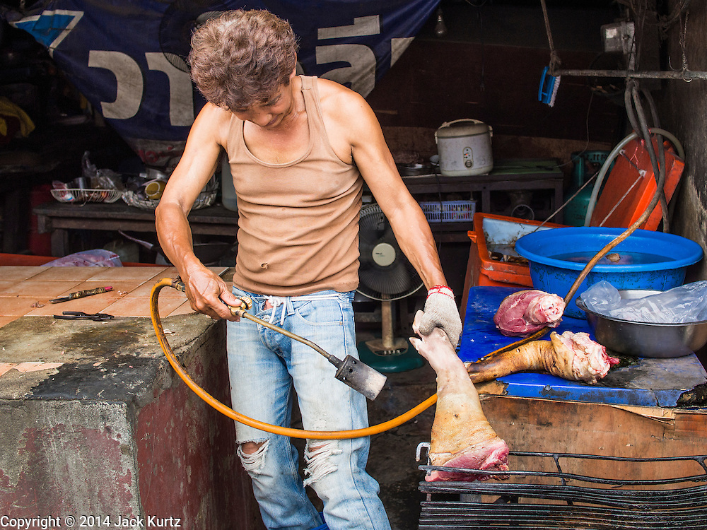 30 AUGUST 2014 - BANGKOK, THAILAND:     A butchers scorches the hair off of a pork leg in a market near the Thonburi train station in Bangkok.    PHOTO BY JACK KURTZ