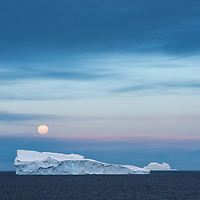 A full moon rises above an iceberg into a pastel sky filled with whispy clouds near the Lemaire Channel in Antarctica.