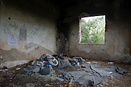 Discarded blankets and clothing in an abandoned house near the Macedonian border. Evzonoi, Greece, March 24, 2016.