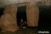 guide rides tube down the Caves Branch River through the Crystal Cave, past cave formations on the grounds of Jaguar Paw Jungle Resort, Cayo District, Belize, Central America MR 335