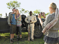 Couple and safari guide posing by jeep young woman taking photograph
