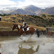 Sarah Liley riding Country Colours in action at the water jump during the Cross Country event at the Wakatipu One Day Horse Trials at the Pony Club grounds,  Queenstown, Otago, New Zealand. 15th January 2012. Photo Tim Clayton