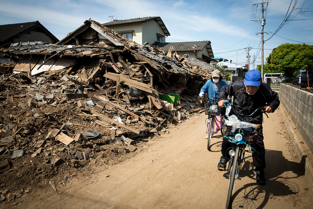 KUMAMOTO, JAPAN - APRIL 20 : A couple is seen through the wreckage of houses on April 20, 2016 in Mashiki town, Kumamoto, Japan. At least 41 people were killed and over 180,000 people were evacuated in the series of earthquakes hitting southwestern Japan since 14 April 2016.<br /> Photo: Richard Atrero de Guzman