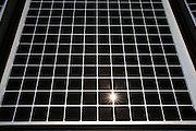 Close-up of a photovoltaic solar energy panel with the sun shining through. This panel, or module, is made up of photovoltaic (PV) cells. PV cells convert sunlight into electrical energy. Photovoltaic panels are an economical, efficient way to produce electricity that does not pollute or contribute to global warming. London, United Kingdom.  (photo by Andrew Aitchison / In pictures via Getty Images)