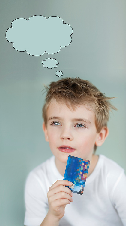 Pensive little boy holding credit card with speech bubble over gray background