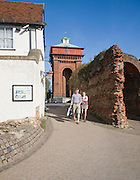 A couple walk past the Roman Balkerne Gate with Jumbo water tower behind, Colchester, Essex, England