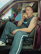 Young man sitting in car with door open smoking cigarette.