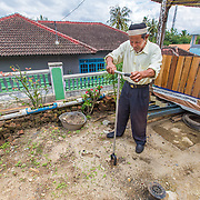 CAPTION: Mr Fadillah, a facilitator at the Biopores Centre in Langkapura Village, demonstrates how a biopore is constructed. LOCATION: Biopores Centre, Langkapura Village, Bandar Lampung, Indonesia. INDIVIDUAL(S) PHOTOGRAPHED: Rusyamsi Fadillah.