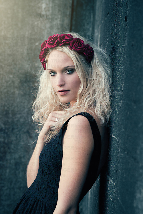 Portrait of a fairy young woman with blonde curly and roses in her hair