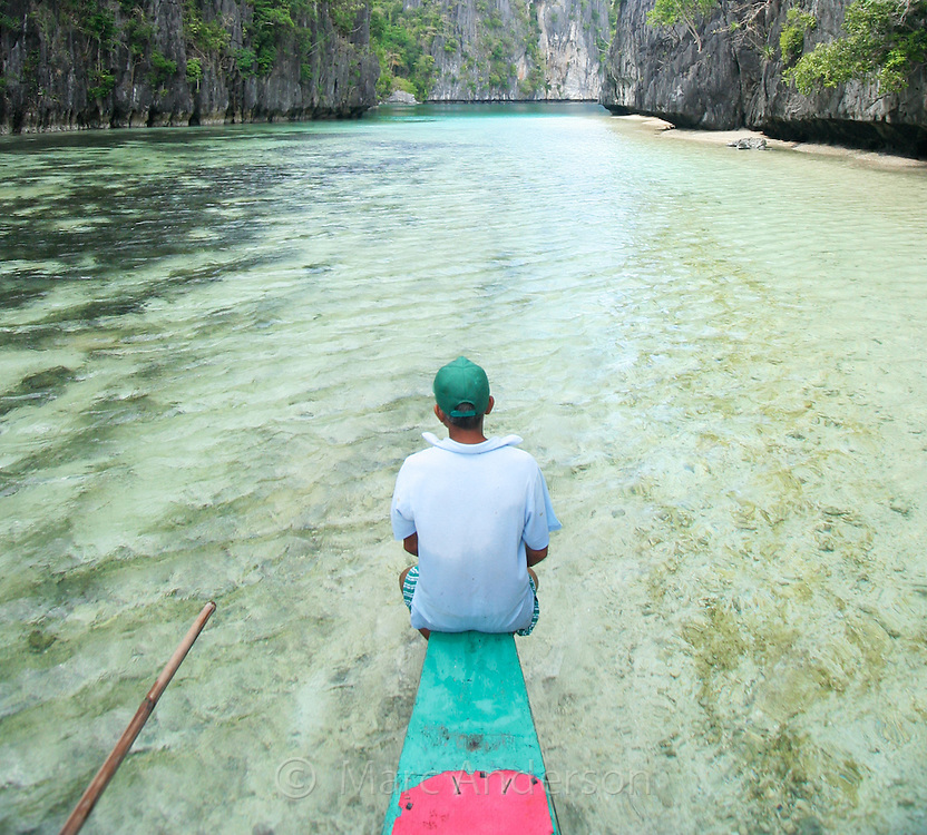 A boatman at the front of a boat entering the Big Lagoon surrounded by limestone cliffs in the Bacuit Archipelago , El Nido, Palawan, Philippines.