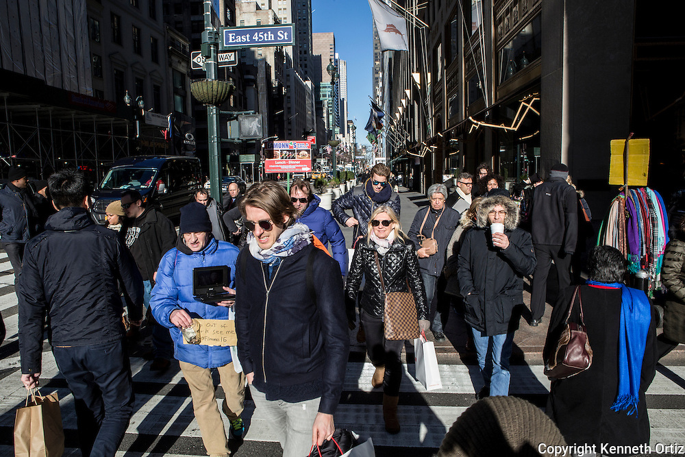 A group of New Yorkers walking down Fifth Avenue on a sunny winter day.