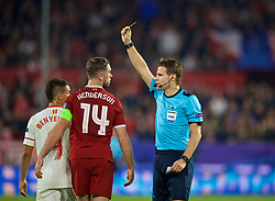 SEVILLE, SPAIN - Tuesday, November 21, 2017: Referee Felix Byrch shows Liverpool's captain Jordan Henderson a yellow card during the UEFA Champions League Group E match between Sevilla FC and Liverpool FC at the Estadio Ramón Sánchez Pizjuán. (Pic by David Rawcliffe/Propaganda)