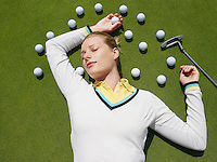 Young woman lying on green surrounded with golf balls view from above