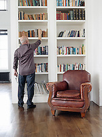 Middle-aged man taking book from shelf back view