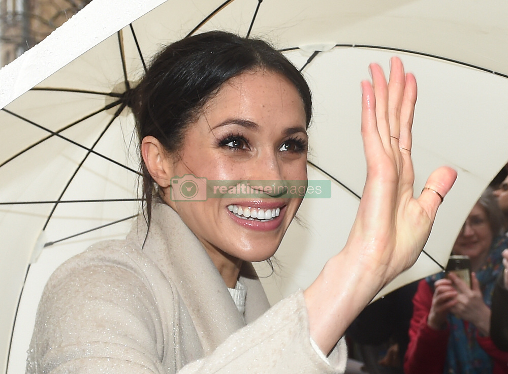 Meghan Markle shelters from the rain under an umbrella as she waves to wellwishers during a walkabout in Belfast after a visit to the Crown Bar in the city centre.