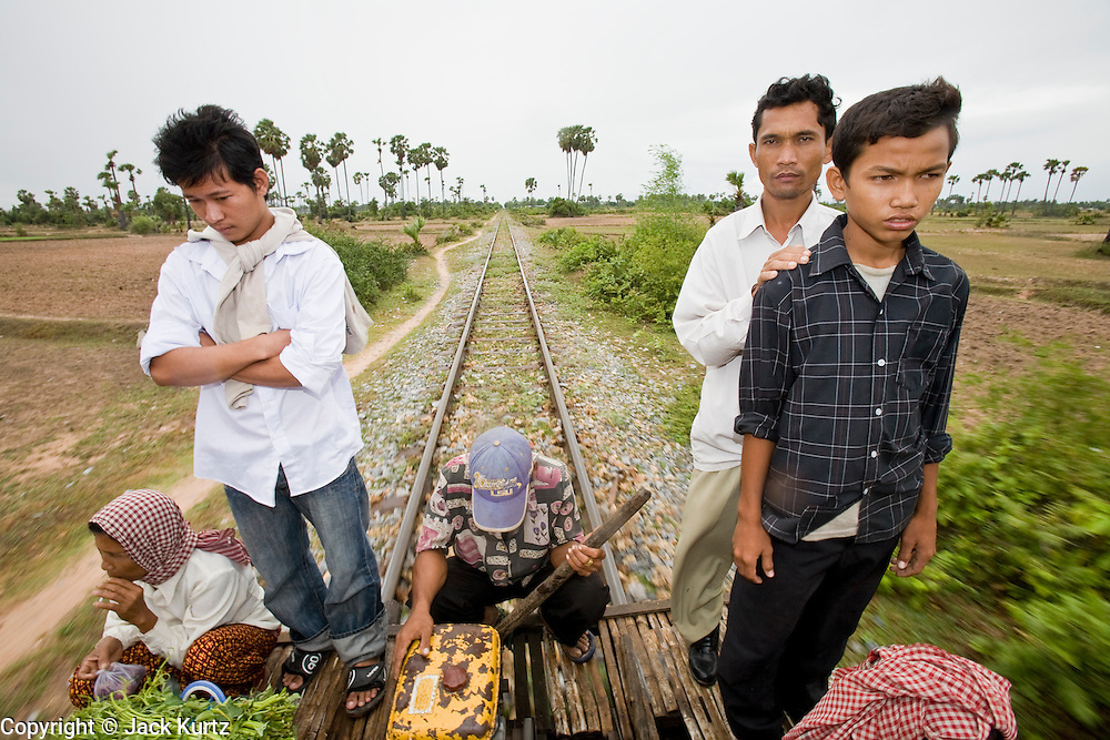 "01 JULY 2006 - PHNOM PENH, CAMBODIA: Passengers ride a bamboo train while the train driver (center) operates it in rural Cambodia. The ""bamboo trains"" run along the government tracks in rural Cambodia. Bamboo mats are fitted over wheels which ride on the rails. The contraption is powered by a either a motorcycle or lawn mower engine. The Cambodian government would like to get rid of the bamboo trains, but with only passenger train in the country, that runs only one day a week, the bamboo trains meet a need the government trains do not. While much of Cambodia's infrastructure has been rebuilt since the wars which tore the country apart in the late 1980s, the train system is still in disrepair. There is now only one passenger train in the country. It runs from Phnom Penh to the provincial capitol Battambang and it runs only one day a week. It takes 12 hours to complete the 190 mile journey.  Photo by Jack Kurtz / ZUMA Press"