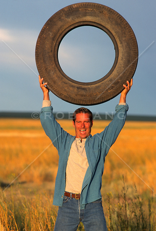 Man outdoors in a field enjoying holding a large tire above his head