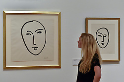 "© Licensed to London News Pictures. 01/08/2017. London, UK. A staff member views (L to R) ""Large Face (Mask)"", 1952, and ""Large Mask"", 1948.  Preview of ""Matisse in the Studio"", at the Royal Academy of Arts, Piccadilly, the first exhibition to consider how the personal collection of treasured objects of Henri Matisse were both subject matter and inspiration for his work.  Around 35 objects are displayed alongside 65 of Matisse's paintings, sculptures, drawings, prints and cut-outs.  The exhibition runs 5 August to 12 November 2017.  Photo credit : Stephen Chung/LNP"