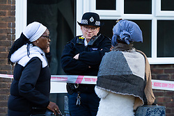 Aunt Lorna, 57, of the victim and a friend talk with a police officer on the cordon following the murder on October 17th of Ian Tomlin, 46, at a high-rise Doddington Estate in Battersea, South London . Battersea, London, October 18 2018.