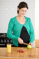 Pregnant woman preparing food in kitchen