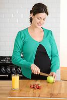 Pregnant woman preparing food in kitchen