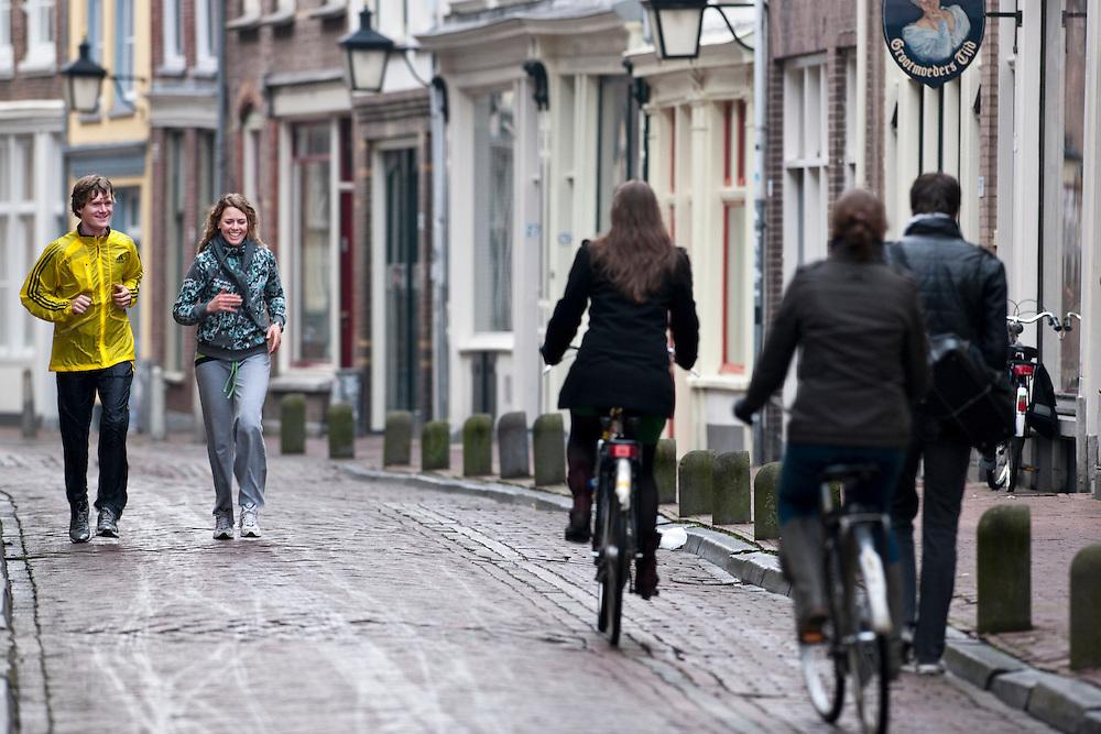 Een man en vrouw zijn aan het hardlopen door de Haverstraat in Utrecht