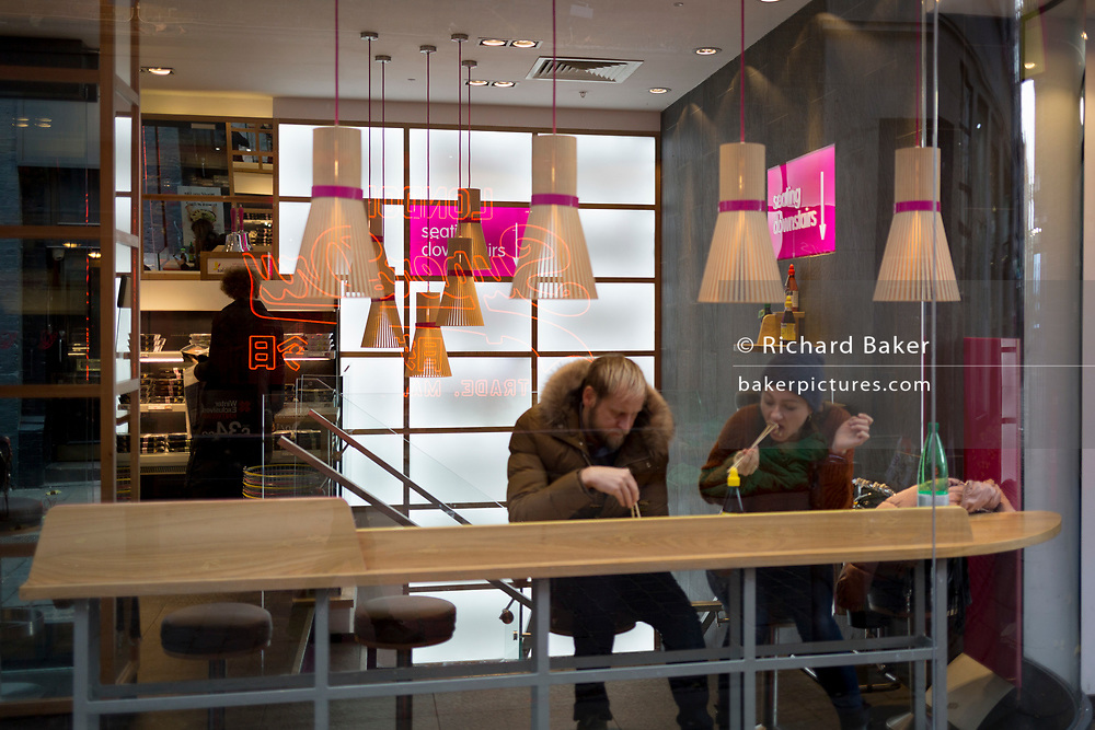 Customers sit eating lunch in the window of retailer Itsu, on 22nd November 2017, in London England.