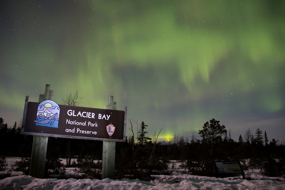 Northern lights (aurora borealis) dance in green and purple over the entrance sign to Glacier Bay National Park.