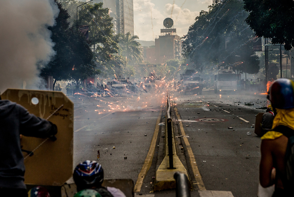 """CARACAS, VENEZUELA - MAY 20, 2017:  Anti-government protesters fire small firework rockets from what they call a """"torta"""" (a big box of fireworks) at National Guard soldiers who responded by heavily tear gassing and firing rubber bullets and buckshot at them. The streets of Caracas and other cities across Venezuela have been filled with tens of thousands of demonstrators for nearly 100 days of massive protests, held since April 1st. Protesters are enraged at the government for becoming an increasingly repressive, authoritarian regime that has delayed elections, used armed government loyalist to threaten dissidents, called for the Constitution to be re-written to favor them, jailed and tortured protesters and members of the political opposition, and whose corruption and failed economic policy has caused the current economic crisis that has led to widespread food and medicine shortages across the country.  Independent local media report nearly 100 people have been killed during protests and protest-related riots and looting.  The government currently only officially reports 75 deaths.  Over 2,000 people have been injured, and over 3,000 protesters have been detained by authorities.  PHOTO: Meridith Kohut"""