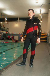 Teenage boy standing at side of public swimming pool wearing wet suit,