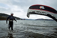 Jeff Yates watches as his friend and kite surfing partner, Scott Owbridge, attempts to get his kite out of the water near the city beach of Lake Coeur d'Alene during an outing Monday.