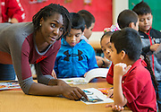 Abiola Wabara checks out a book with a student during a Touchdown Houston Read On literacy program at Ross Elementary School, December 2, 2016.
