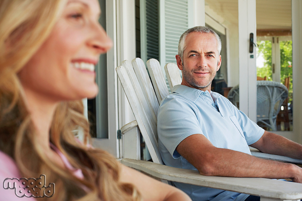 Couple sitting on porch smiling focus on man