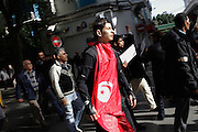 A boy wears a Tunisian flag during a demonstration demanding the dissolution of the new interim governement.