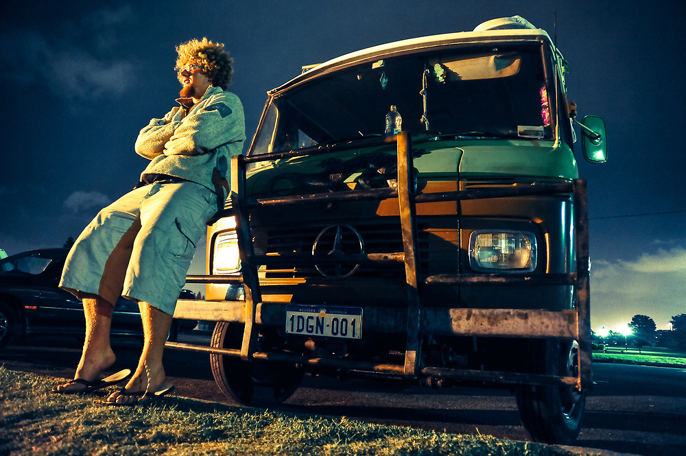 A backpacker leans against his Mercedes campervan on Nobby's Beach in Newcastle, Australia