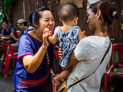 20 MAY 2017 - BANGKOK, THAILAND: A woman who lives in Pom Mahakan greets a neighbor's child in the old fort. The final evictions of the remaining families in Pom Mahakan, a slum community in a 19th century fort in Bangkok, have started. City officials are moving the residents out of the fort. NGOs and historic preservation organizations protested the city's action but city officials did not relent and started evicting the remaining families in early March.        PHOTO BY JACK KURTZ