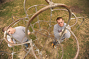Two students clean up playground equipment at a park in East Liverpool East Liverpool as part of an alternative spring break, in which students spend a week performing community service.