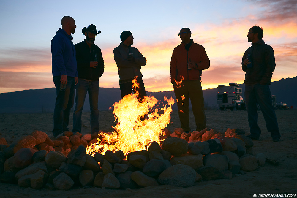 A group of RV nomads gathered around a camp fire in the Mojave Desert of California.