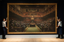 © Licensed to London News Pictures. 27/09/2019. London, UK. Sotheby's staff hold a painting titled Devolved Parliament, 2009, by artist Banksy. The painting depicts MP's in the houses of Parliament with an estimate of £1.5-2 million. The work is part of the Sotheby's contemporary art auction. Photo credit: Ray Tang/LNP