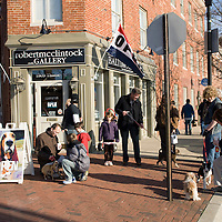 """People and their dogs gather outside the Robert McClintock Studio & Gallery to mingle and look at artwork by the local artist, 1809 Thames Street, Baltimore, Maryland, USA.  The artist melds photography and digital painting to create his vibrant """"Baltimore Seen"""" works and other collections of work including portraits of dogs."""