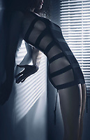 Sexy edgy fashion photo of a beautiful woman in stripy black underwear standing with her body arched in a seductive curve in dim window light