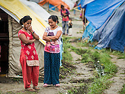05 AUGUST 2015 - KATHMANDU, NEPAL: Women chat between tents in a large Internal Displaced Person (IDP) Camp in the center of Kathmandu. The camp is next to one the most expensive international hotels in Kathmandu. More than 7,100 people displaced by the Nepal earthquake in April live in 1,800 tents spread across the space of three football fields. There is no electricity in the camp. International NGOs provide water and dug latrines on the edge of the camp but the domestic waste water, from people doing laundry or dishes, runs between the tents. Most of the ground in the camp is muddy from the running water and frequent rain. Most of the camp's residents come from the mountains in northern Nepal, 8 - 12 hours from Kathmandu. The residents don't get rations or food assistance so every day many of them walk the streets of Kathmandu looking for day work.    PHOTO BY JACK KURTZ