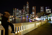 Nightlife along Singapore River. Man with mobile phone on Elgin Bridge.