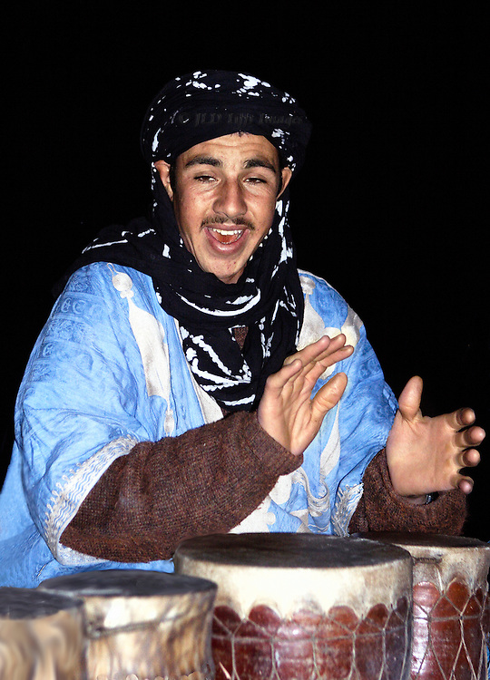 Bedouin drummer joyfully hammers his drums in a nighttime performance in the desert near Erfoud, Morocco.  He is making a joyful noise.