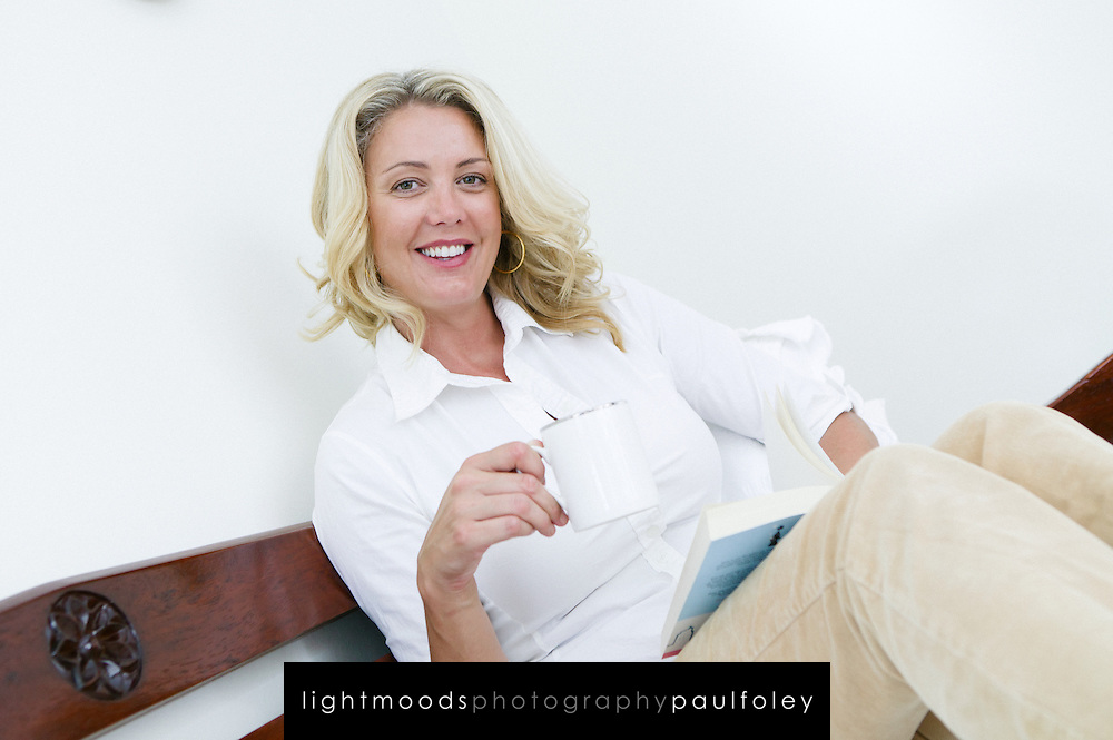 Smiling woman, looking to camera,holding coffee,relaxing on couch